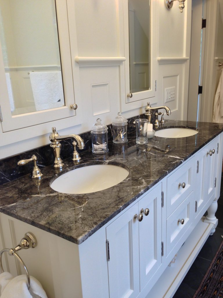His' and Hers' bathroom sinks with dark stone contrasting the white walls