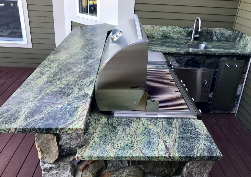 outdoor grill station with green and blue stone top and rough rock sides