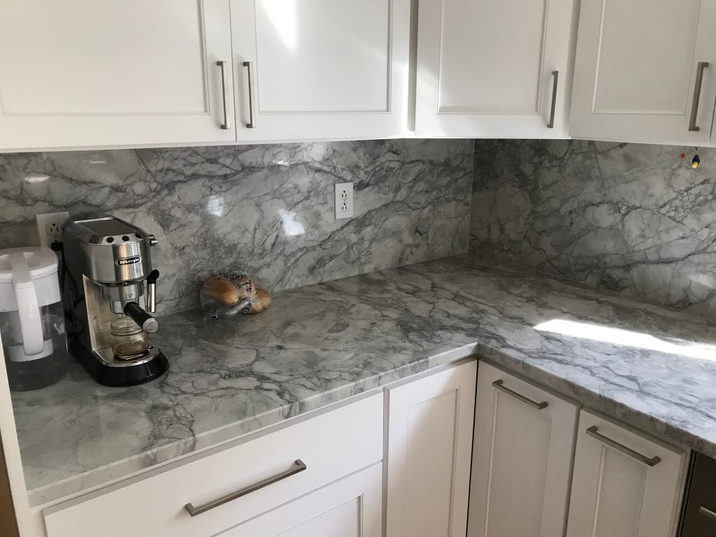 Single L countertop cut with tall backsplash of stone