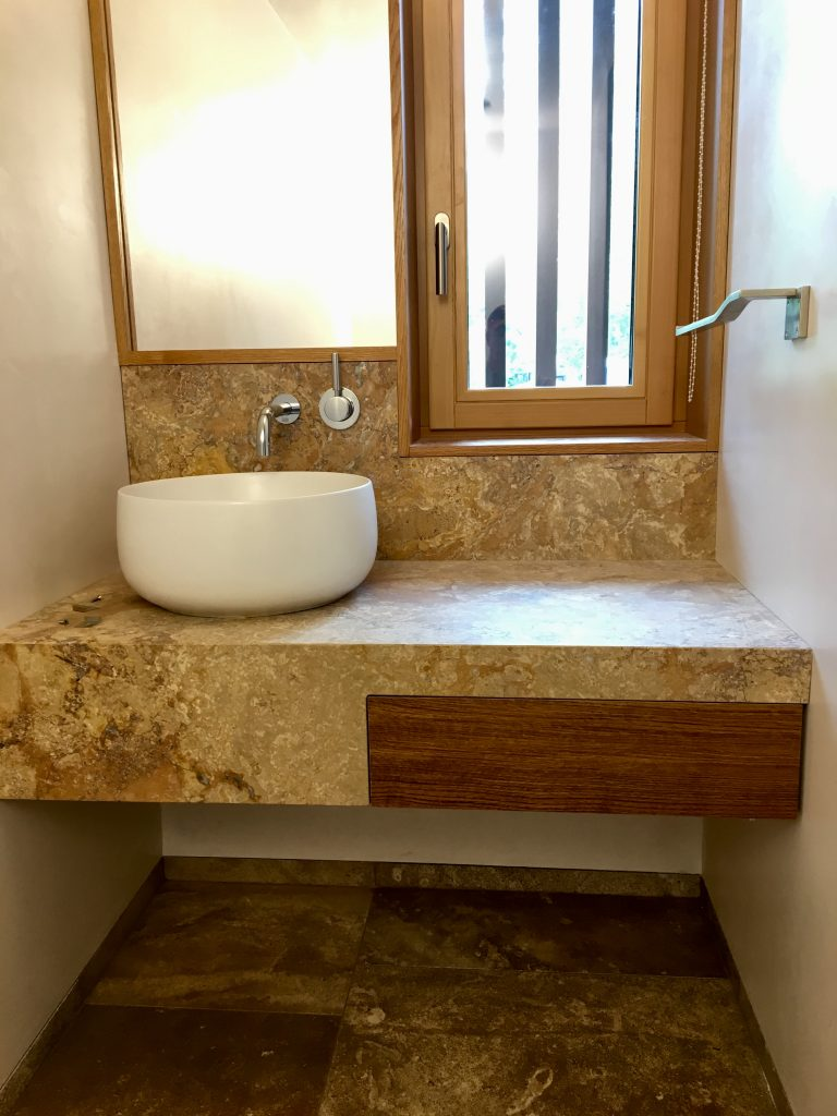 stone bathroom sink area with wood cut out for drawer