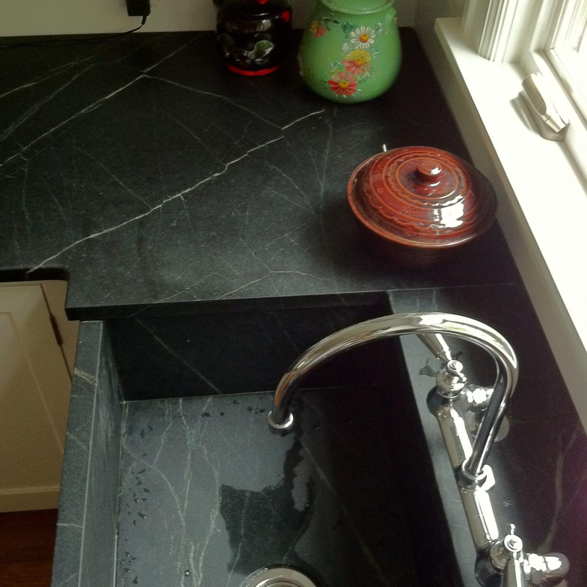 Dark stone countertop with stone sink basin