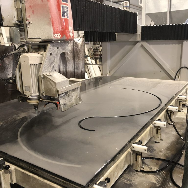 Water jet machine cutting thick stone with curved edges